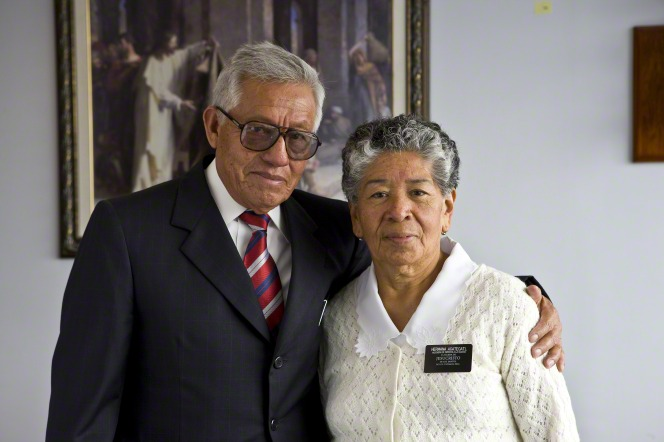 A missionary couple serving in Mexico City, Mexico, at the Church employment resource center, with the elder putting his arm around his wife.