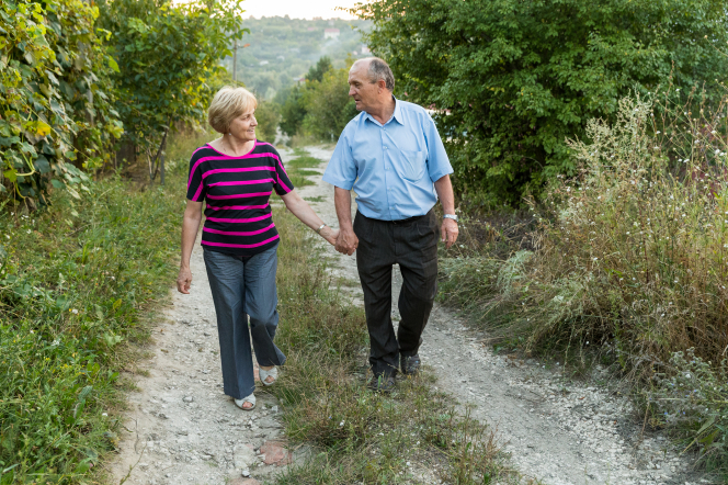An elderly couple in Moldova, smiling while looking at each other and holding hands as they walk down a dirt road with green trees on each side.
