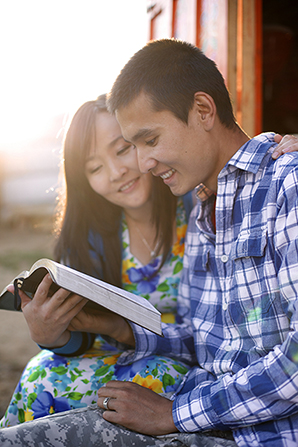 A woman in a floral dress sits next to a man in a plaid shirt as they read the scriptures together outside in Mongolia.