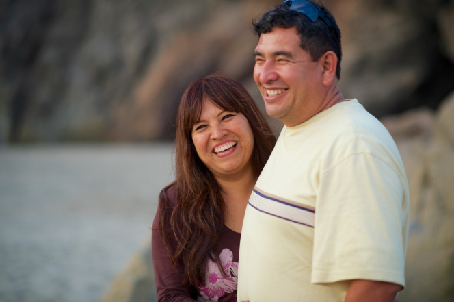 A woman with brown hair and a brown shirt with a flower design smiles and stands next to her husband in a yellow shirt on a beach in Peru.