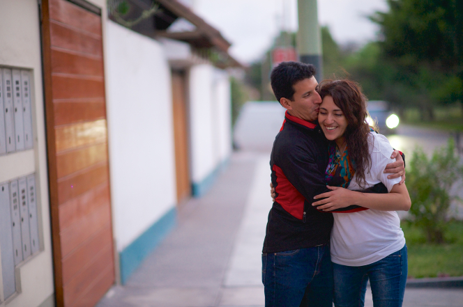A man in a black shirt embraces his wife and kisses her forehead as she smiles while standing outside on a sidewalk in Peru.