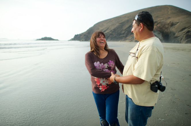A woman with brown hair blowing in the wind laughs while holding hands with her husband in a yellow shirt as they stand near a mountain on a Peru beach.