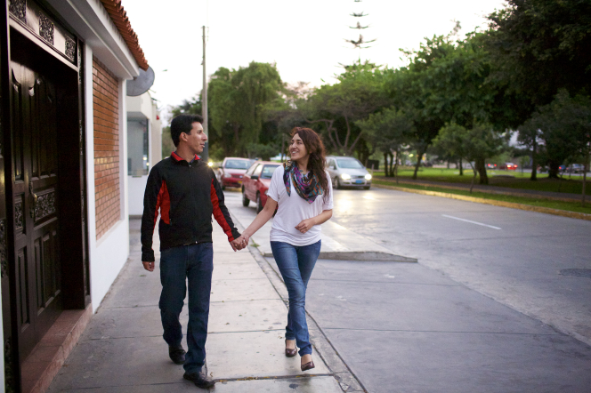 A husband in a black long-sleeve shirt walking down a sidewalk and holding hands with his wife in a white shirt and scarf, with cars in the background.