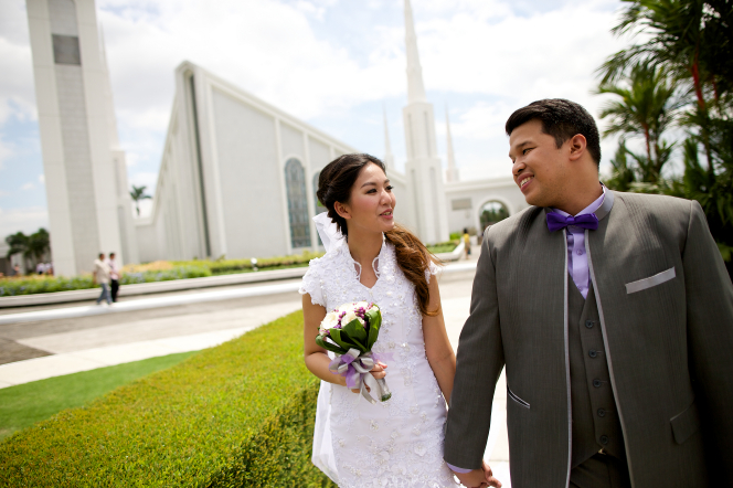 A bride in a lace dress with a bouquet of flowers holds hands with the groom in a gray suit as they walk outside of the Manila Philippines Temple.