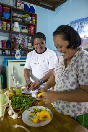 A husband and wife from the Philippines smile while standing next to a table and cutting food together at home in their kitchen.