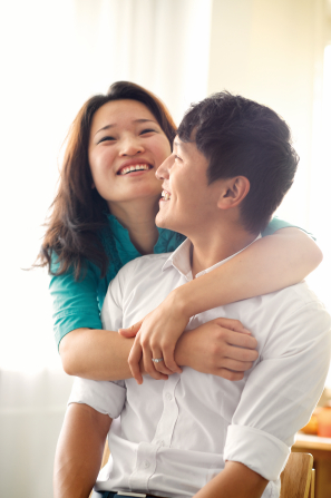 A portrait of a young Asian couple, with the man in a white shirt sitting down and his wife in a blue shirt standing and hugging him from behind.