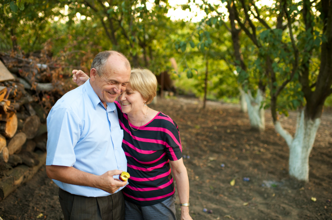 An elderly woman standing with her arm over her husband's shoulder while he holds a piece of sliced fruit in an orchard in Romania.