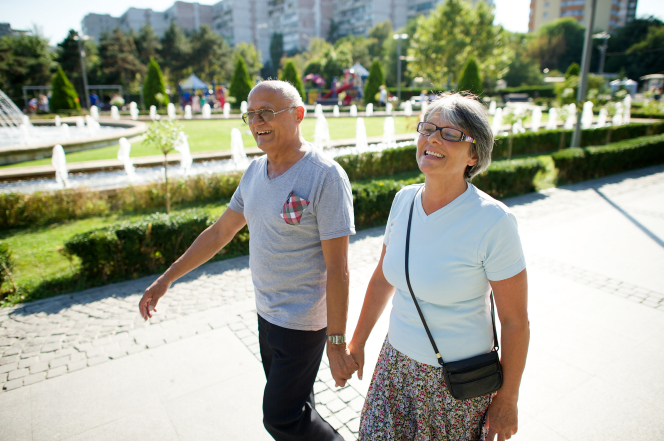 An elderly couple from Romania holding hands and walking down a sidewalk with the sun shining on their backs.