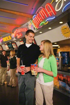 A teenage couple standing in the lobby of a movie theater, with the young man holding a drink and the young woman holding popcorn.