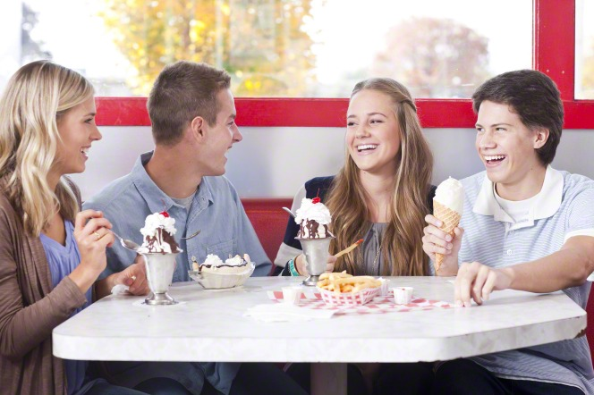 Two young men and two young women sit at a table booth while eating ice cream and laughing together.