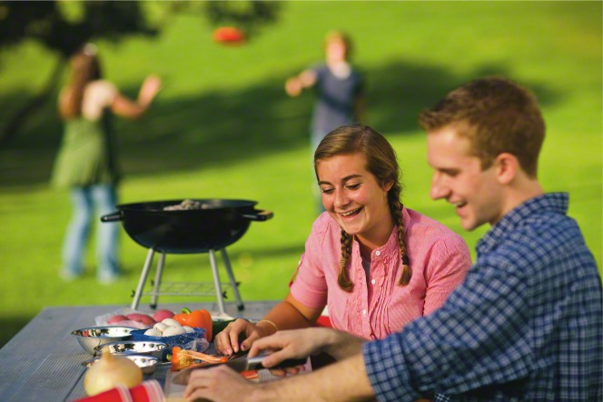A young man in a blue paid shirt and a young woman in a pink blouse cut vegetables at a picnic table for a barbecue at the park.