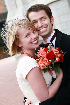 A portrait of a bride and groom embracing and smiling on their wedding day, while the bride holds a bouquet of flowers.