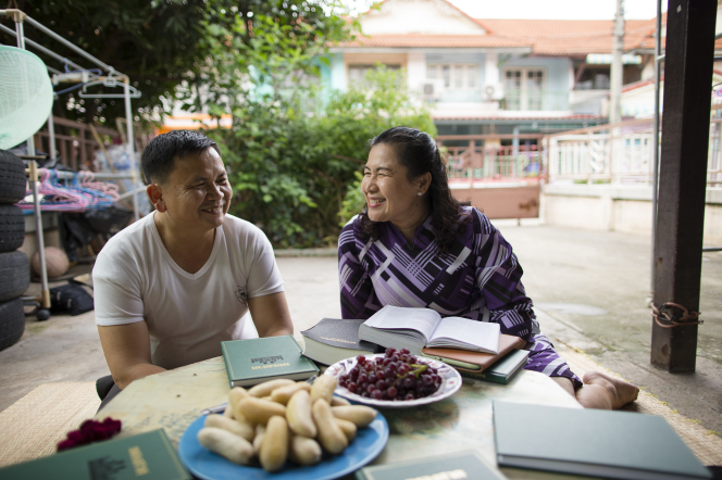 A husband and wife from Thailand sit next to each other at a table covered with plates of fruit, hymnbooks, and other gospel books.