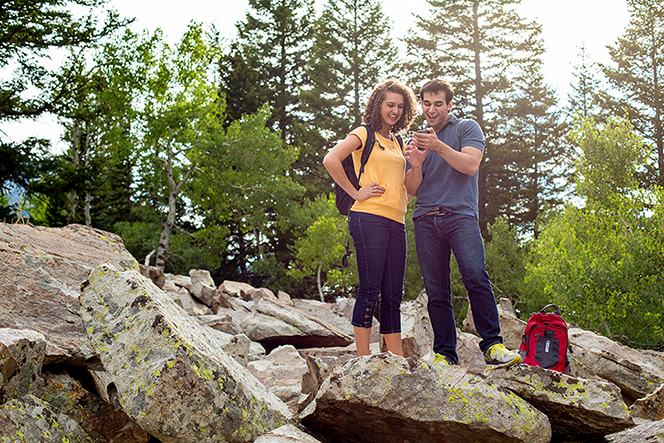 A couple on a hike, standing on a rock near trees while looking at a small device together.