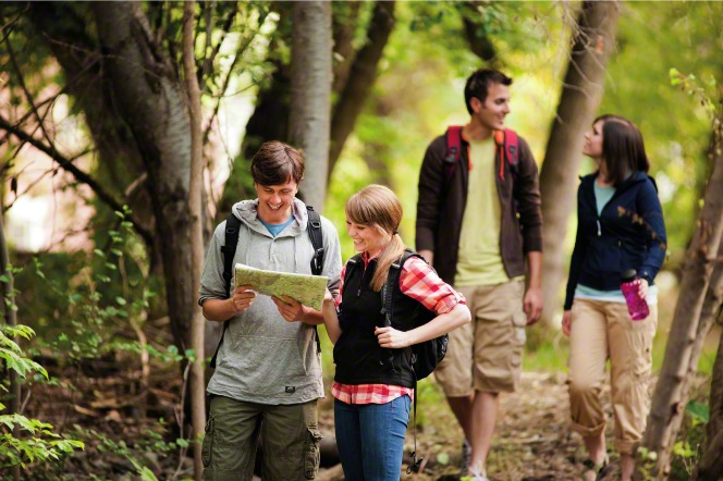 While hiking, one couple stands looking at a map together and another couple talks behind them.