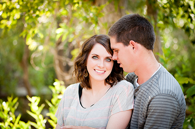 An engagement picture of a young man embracing a young woman while standing outside near overhanging trees.