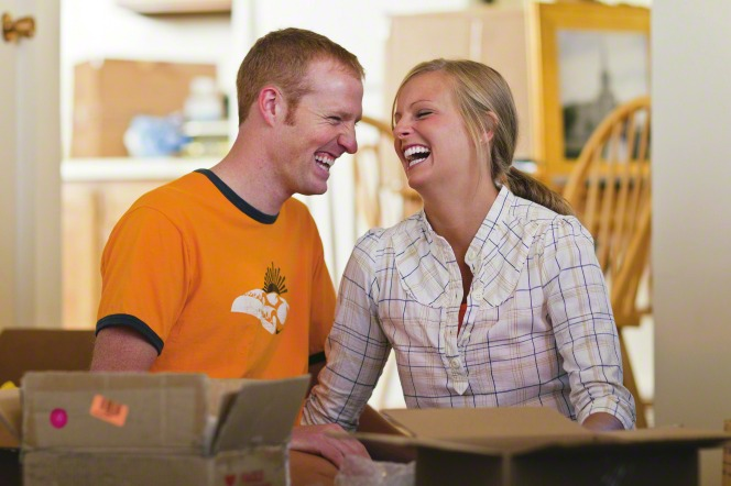 A newly married couple sitting at a table while unpacking boxes and laughing together in their new home.