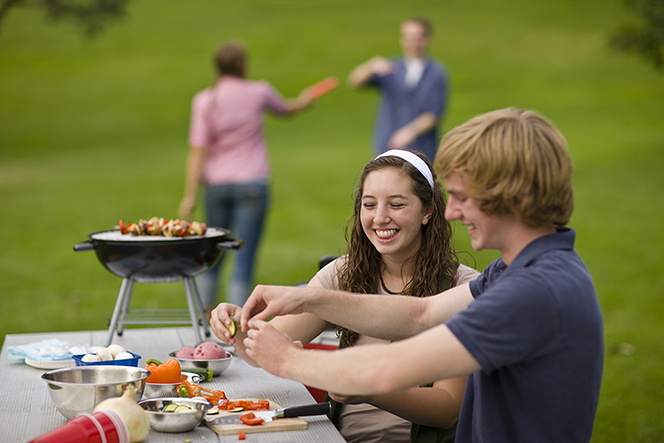 A teenage couple at a picnic table in the park preparing food to cook on a grill, with a couple playing Frisbee behind them.