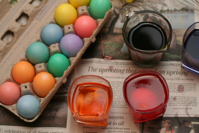 Four cups full of colorful dye sitting on top of a newspaper next to a dozen pastel-colored eggs in a cardboard carton.