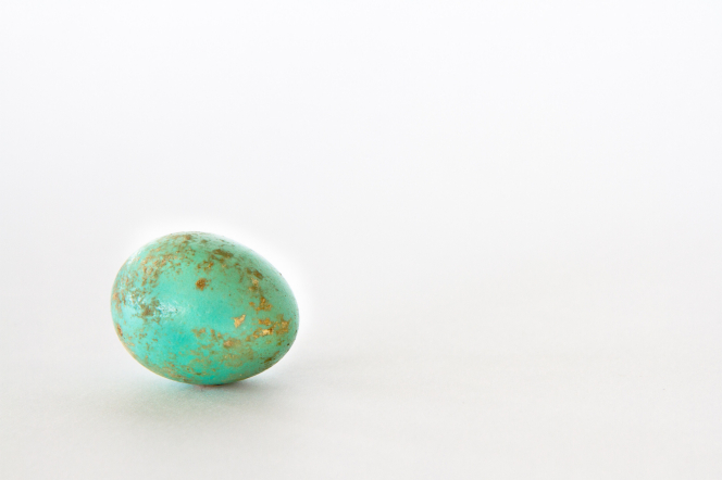 A teal-colored Easter egg that has been partially speckled by gold paint or leafing, resting on a plain white background.