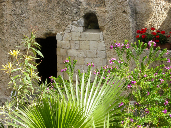 The entrance to the Garden Tomb in Jerusalem, seen beyond large plant fronds and purple flowers growing on a bush.