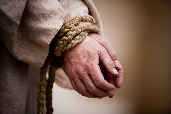 A depiction Christ's hands tied together tightly with a thick braided rope.