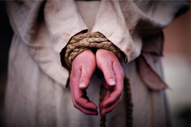 The hands of Christ tied together with a brown braided rope.