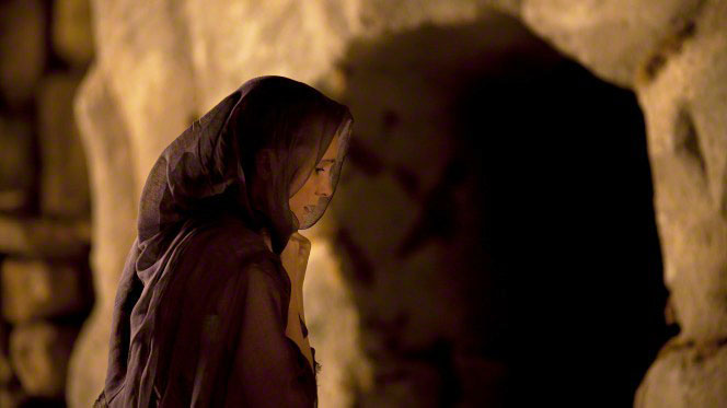 A woman with a purple shawl, standing outside of the entrance to an empty tomb.