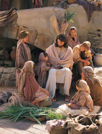 Seven children in biblical-era clothing sit and interact with a man dressed as Jesus Christ.