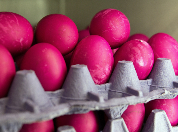 A pile of fresh Easter eggs that have been dyed bright pink between stacks of egg carton cardboard.