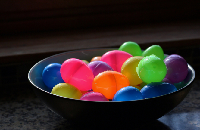 A bowl full of green, pink, purple, yellow, blue, and orange plastic Easter eggs.