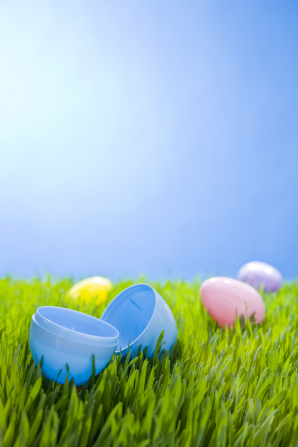 Four plastic Easter eggs lying on a patch of bright green grass under a clear blue sky.