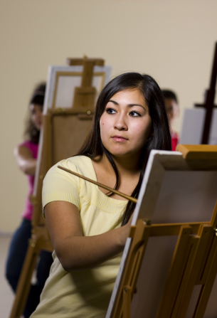 A young woman with long black hair sits at an easel and holds a paintbrush in her hand. Other students are seen in the background behind easels.