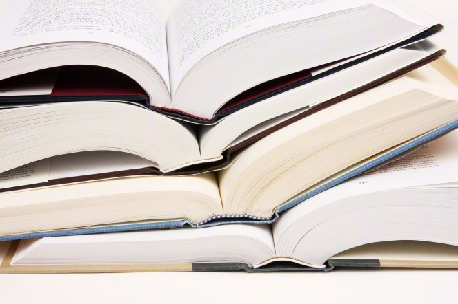 A stack of four books with white pages lie open, one on top of the other.