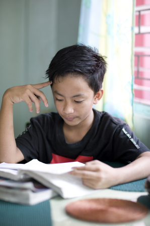 A young boy with short black hair sits at a table in his home and reads from a textbook, with a pile of books on the table.
