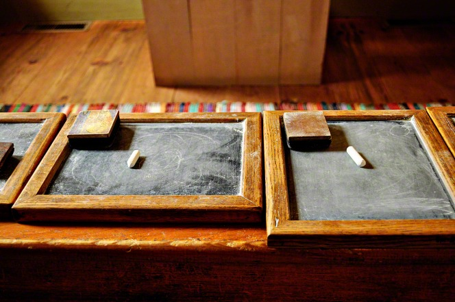 Small chalkboards with wooden frames and small erasers and a piece of chalk set on top of each are lined up on a wooden bench.