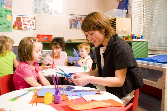 A woman sits at a children's table covered in colored construction paper and helps a little girl cut the construction paper.