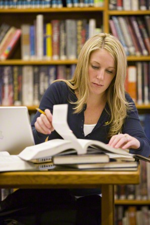 A young woman with long blond hair and a blue shirt sits at a table in a library and flips through a book, with a bookshelf in the background.