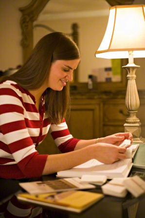 A young woman with long brown hair and a red and white striped sweater sits at a desk with books open and reads next to a lamp that is turned on.