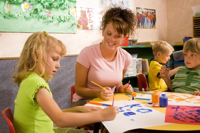 A woman in a pink shirt and curly hair sits at a table with a boy and a girl and helps them paint on white paper with paintbrushes and watercolor.