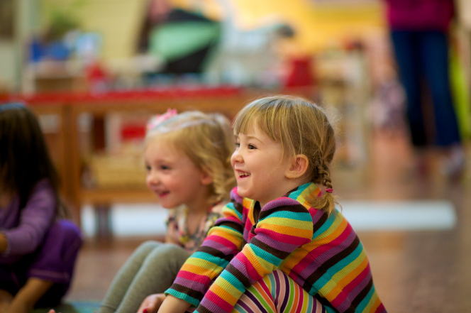 A little girl with pigtails and rainbow-striped clothing sits next to another little girl on the floor in a classroom at an elementary school.