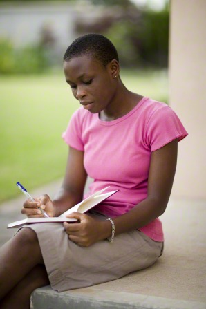 A young woman in Ghana, wearing a pink shirt and a khaki skirt, sits on a step outside and writes with a pen in a journal.