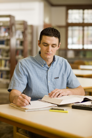 A young man in a blue button-up shirt sits at a table in a library and writes notes in a spiral notebook while reading from a large textbook.