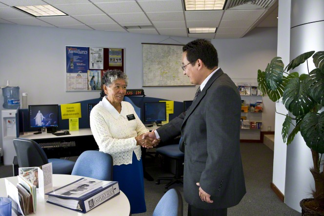 A senior sister missionary in a sweater and skirt shakes hands with a young man in a suit at the LDS employment resource center in Mexico.