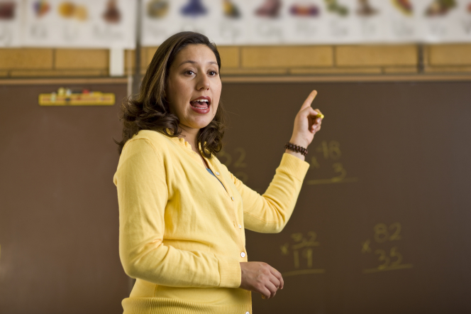 A female teacher with brown hair and a yellow sweater stands at the front of a classroom and points to the blackboard behind her.