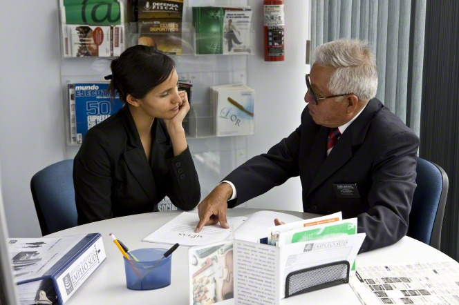 A young woman sits at a table with a senior elder missionary and reads through a pamphlet at the LDS employment resource center in Mexico.