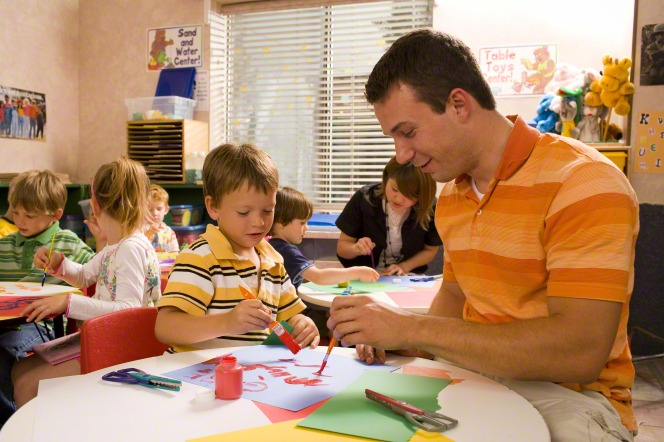 A man sits at a children's table in a classroom with a young boy and helps him paint with acrylic paints on construction paper.