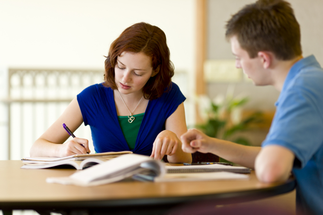 A young woman with short red hair and a blue and green shirt sits at a round table and takes notes in a notebook as a young man in a blue shirt sits next to her.