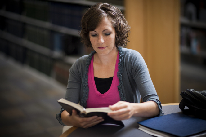 A young woman with curly, short brown hair sits at a round table in a library and reads from a book, with bookshelves in the background.