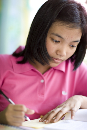 A young woman in a pink polo shirt and short black hair sits at a table and holds a pen while doing a homework assignment out of a book.